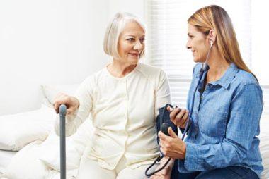 Eine Pflegerin des Pflegedienstes Hermine untersucht eine Patientin.