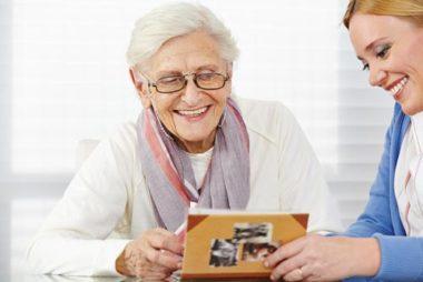 Seniorin lest in einem Buch, unterstützt durch den Pflegedienst Hermine.